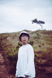 Portrait of a young asian girl wearing glasses and casual clothes looking at the distance. Outdoors shot with blurred out of focus background at Dalat, Vietnam