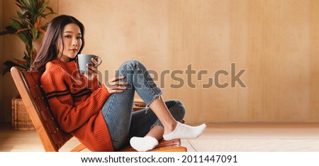Portrait of a young Asian woman wearing a sweater. She inhaled the scent and drank the winter morning coffee. She smiles and enjoys being relaxed at home. Stockfoto ©