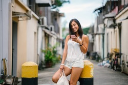 Portrait of a young, athletic, attractive and cute Chinese Asian girl using her smartphone on a street in Asia during the day. She is tanned, petite and relaxed.