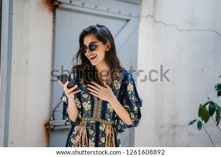 Portrait of a young, attractive and beautiful Indian Asian woman wearing a dress and sunglasses with her smartphone. She looks surprised and delighted and is smiling as she looks at her phone. #1261608892