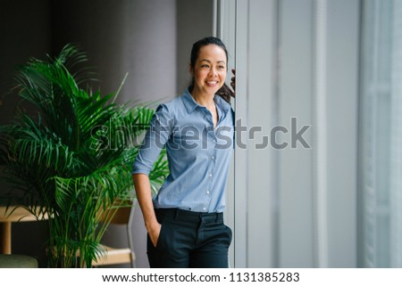 Portrait of a young, attractive and confident Chinese Asian business woman in a meeting room during the day. She is standing by the glass windows and smiling as she leans on the window ledge.  #1131385283