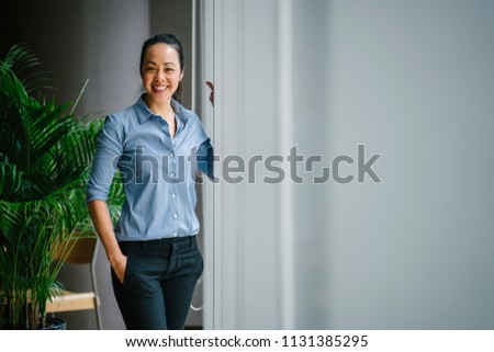 Portrait of a young, attractive and confident Chinese Asian business woman in a meeting room during the day. She is standing by the glass windows and smiling as she leans on the window ledge.