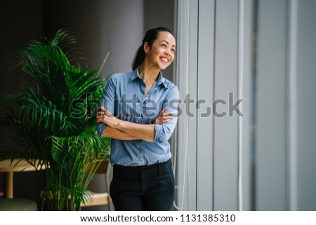 Portrait of a young, attractive and confident Chinese Asian business woman in a meeting room during the day. She is standing by the glass windows and smiling as she leans on the window ledge.  #1131385310