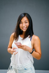 Portrait of a young, attractive and tanned Chinese Asian woman against a grey background as she uses her smartphone. She is smiling in a candid way as she taps on her phone.