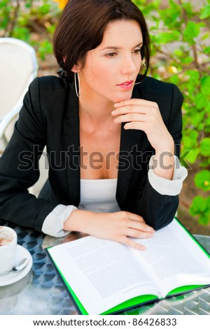 Portrait of a young attractive business woman sitting at outdoor cafe and reading book while drinking coffee