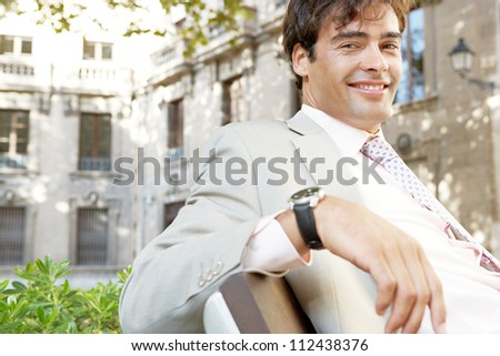 Portrait of a young attractive businessman sitting on a wooden bench in a classic city, smiling.