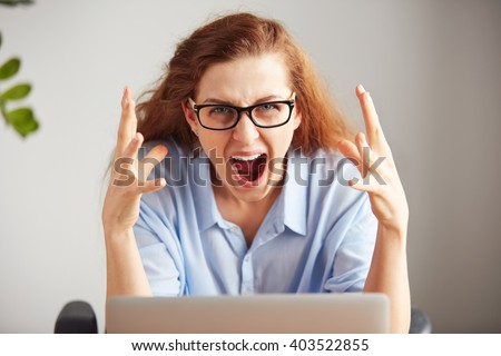 Portrait of a young attractive businesswoman with frustrated look working on laptop at  office. Outraged screaming freelance student looking at camera with desperate expression: I hate this computer