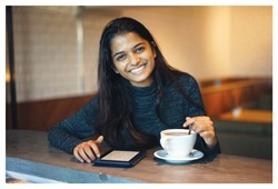 Portrait of a young attractive Indian woman sitting at a table in a cafe enjoying a hot coffee and a kindle read. She is casually and naturally smiling up from her kindle.