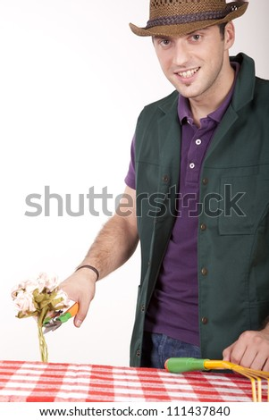 Portrait of a young attractive male gardener checking a flower. - stock photo