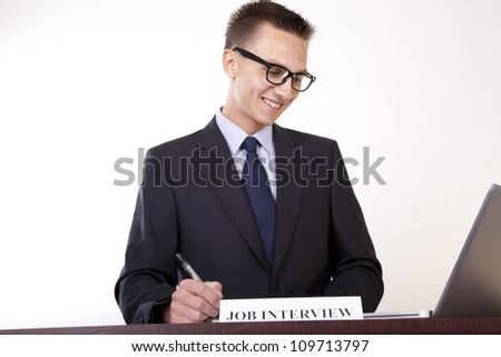 Portrait of a young attractive male secretary with a sign job interview.