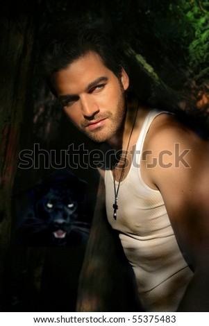 Portrait of a young attractive man in forest with panther lurking in the shadows