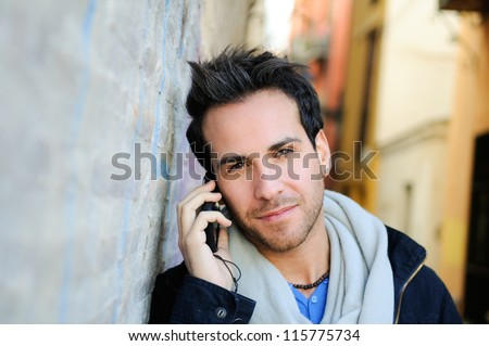 Portrait of a young attractive man in urban background talking on mobile phone