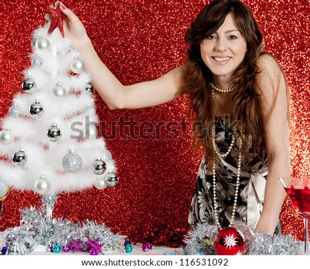 Portrait of a young attractive woman decorating a small christmas tree while standing in front of a red glitter background.