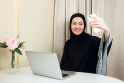Portrait of a young attractive woman in hijab making selfie photo on smartphone.