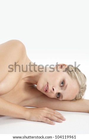 Portrait of a young attractive woman laying naked on a white background.