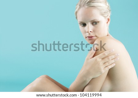 Portrait of a young attractive woman sitting down naked on a blue background.