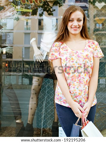Portrait of a young attractive woman standing by a store window with manikins and city buildings reflections holding paper shopping bags and smiling on holiday. Consumer outdoors lifestyle.