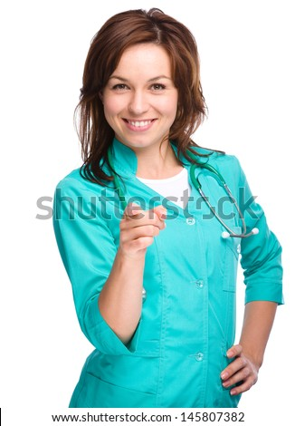 Portrait of a young attractive woman wearing doctor uniform and pointing at you, isolated over white
