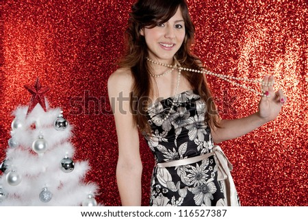 Portrait of a young attractive woman with a small christmas tree pulling her pearls necklace while standing in front of a red glitter background.