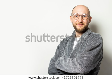 Portrait of a young bald man with a beard in a dressing gown and glasses with arms crossed on his chest on an isolated light background. Emotional face Stock foto ©