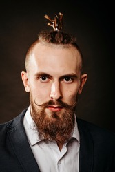 Portrait of a young bearded brutal hipster man, with a long mustache in the studio on a dark background