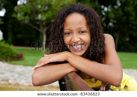 Portrait of a young beautiful african american woman sitting on a bench