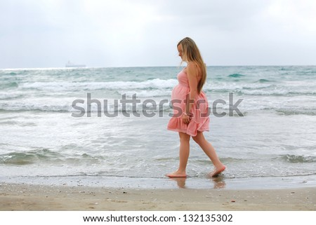 Portrait of a young beautiful blond pregnant woman posing at beach on sea background.