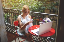 Portrait of a young beautiful blonde women chatting on her mobile phone while resting after work on laptop computer, charming female using cell telephone while sitting with net-book on a home terrace