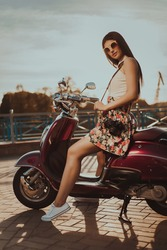 Portrait of a young beautiful brunette with a camera in glasses and a dress in the street at sunset with a moped