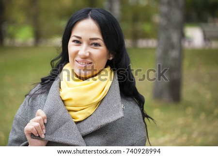 Portrait of a young beautiful brunette woman in gray coat in autumn park