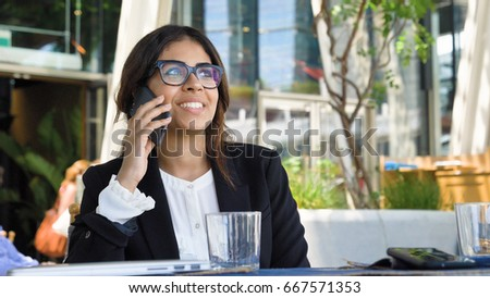 Portrait of a young beautiful business woman (student) in a suit, glasses, sitting at a table, talking on the phone, drinking coffee. Concept: new business, communication, Arab, banker, manager, call. #667571353