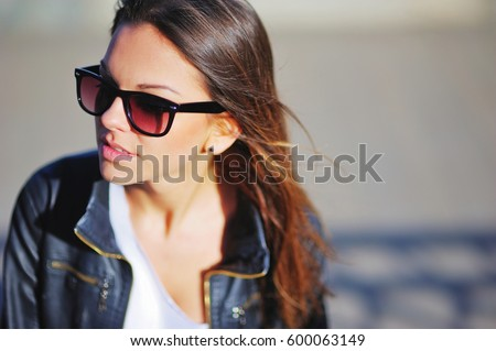 Portrait of a young beautiful confident girl in sunglasses and a black jacket with long silky hair on a grey background, blurred focus, close-up. #600063149