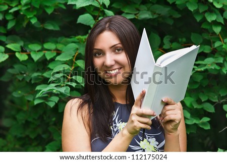 portrait of a young beautiful dark-haired smiling girl with a book