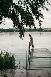 Portrait of a young beautiful European woman with curly hair in a beige dress standing barefoot on a wooden pier by the lake. Nature after the rain. Water, inspiration, girl, rest, relax, loneliness.