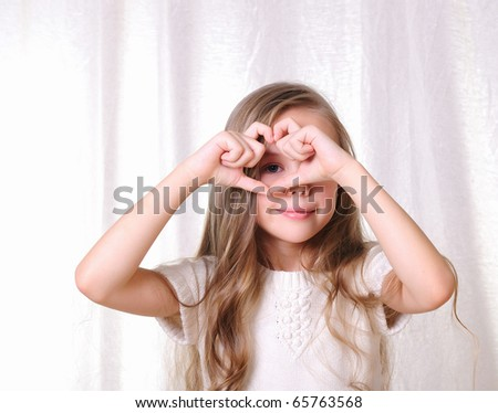 Portrait of a young beautiful girl. A girl makes a gesture in the form of the heart.