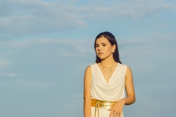 portrait of a young beautiful girl in a white tunic with a gold belt on a blue sky background