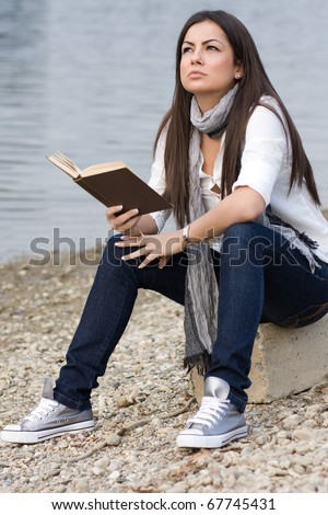Portrait of a young beautiful girl sitting in nature and reading book