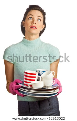 Portrait of a young beautiful housewife holding a pile of dirty dishes and looking fed up. Isolated over white.