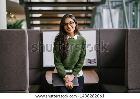 Portrait of a young, beautiful, intelligent and attractive Indian Asian MBA student smiling as she leans in a discussion booth in her campus. She is wearing a preppy outfit and smiling confidently.