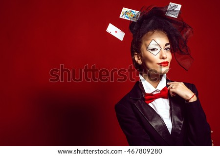 Portrait of a young beautiful lady croupier with an artistic make up joker and flying cards around on the red background. Gamble and casino concept. Studio shot. Copy-space