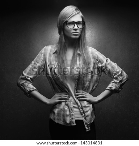Portrait of a young beautiful long-haired woman wearing trendy glasses and casual clothes and posing over metal background. Black and white (monochrome) studio shot