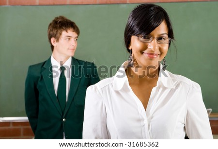 portrait of a young beautiful school teacher, background is her student