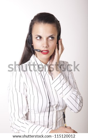 Portrait of a young beautiful secretary with headphones working.