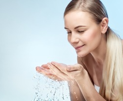 Portrait of a young beautiful woman cleaning her face with fresh cold water, isolated on blue background, morning freshness, removing makeup, health and beauty care concept