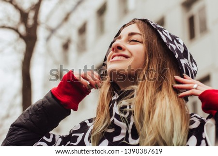 Portrait of a young beautiful woman in a raincoat, walking and dancing in the rain #1390387619