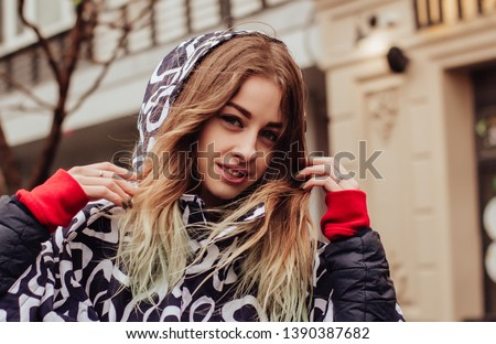 Portrait of a young beautiful woman in a raincoat, walking and dancing in the rain #1390387682