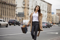 Portrait of a young beautiful woman in beige coat with a bag posing on a background of autumn street