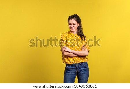 Portrait of a young beautiful woman in studio on yellow background. #1049568881