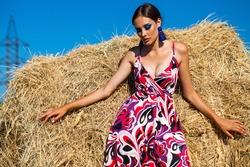 Portrait of a young beautiful woman with bright makeup posing on a mown wheat field