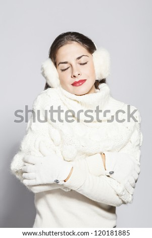 portrait of a young beautiful woman with close eyes, total white winter look. on grey background.